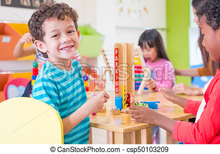 Kindergarten Students Smile When Playing Toy In Playroom At