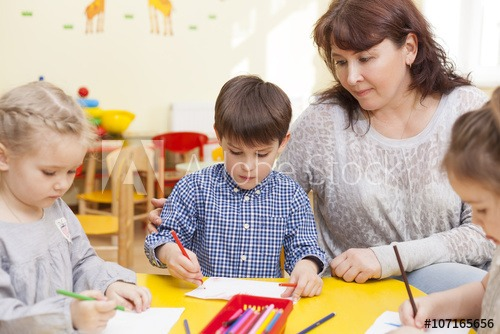 Cute Pupil Of The Kindergarten, Draws At The Yellow Table