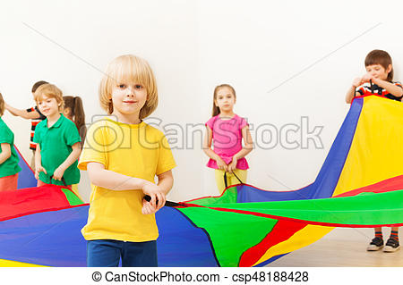 Boy Playing Parachute With Friends In Kindergarten  Portrait Of